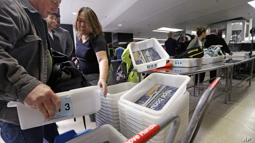 In this photo taken April 6, 2017, passengers reach for bins as they prepare to go through a security check-point at Seattle-Tacoma International Airport, in SeaTac, Washington.