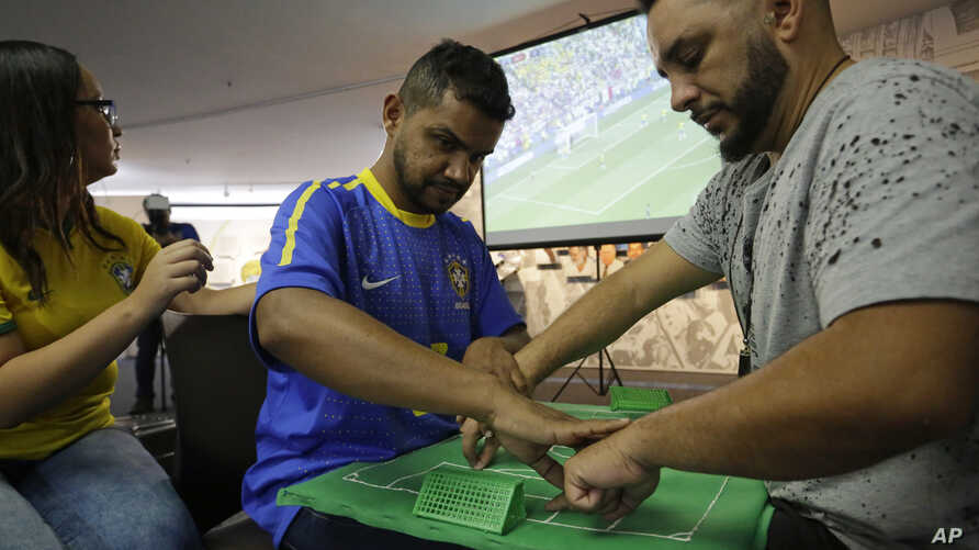 Brazil soccer fan Carlos Junior, who is both deaf and blind, experiences the World Cup match between Brazil and Mexico with the help of an interpreter who uses tactile signing and a model soccer field in Sao Paulo, Brazil, July 2, 2018. Brazil won th