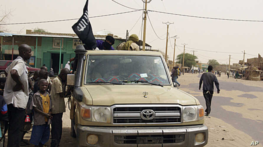 Fighters from the Ansar Dine group, flying the group's black flag, instruct local residents in how to follow Shariah, as they stop in a market area of Timbuktu, Mali, April 14, 2012.