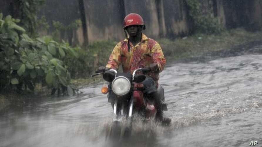 A man ride on motor cycle through a flooded street following a heavy downpour in Lagos, Nigeria, July 11, 2011