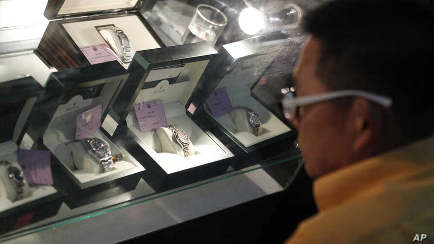 In this March 2, 2015 photo, a Thai visitor examines Rolex watches at the public viewing for an auction of items seized from Lt. Gen. Pongpat Chayapam, in Bangkok, Thailand.