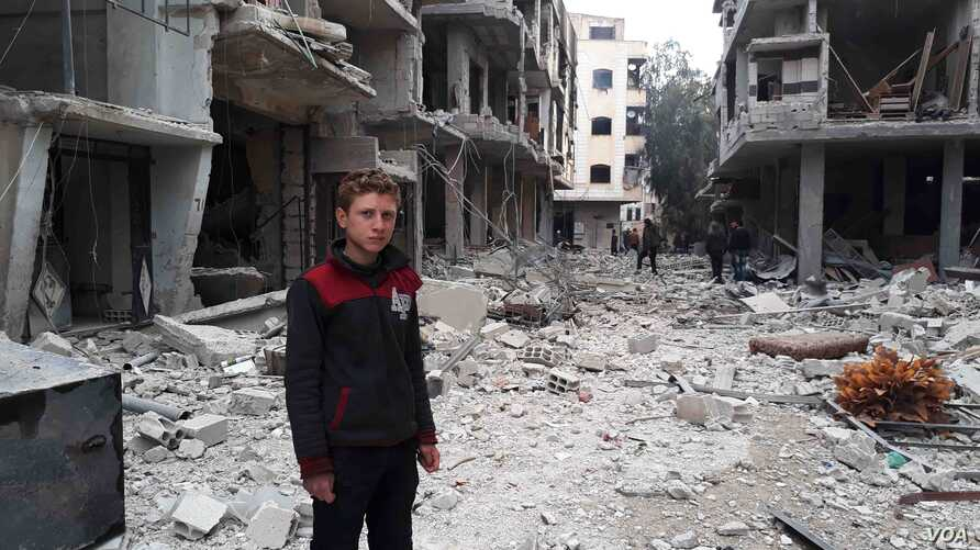Muhammed Najem stands in the rubble of his neighborhood in Arbin, Eastern Ghouta, Feb. 23, 2018.