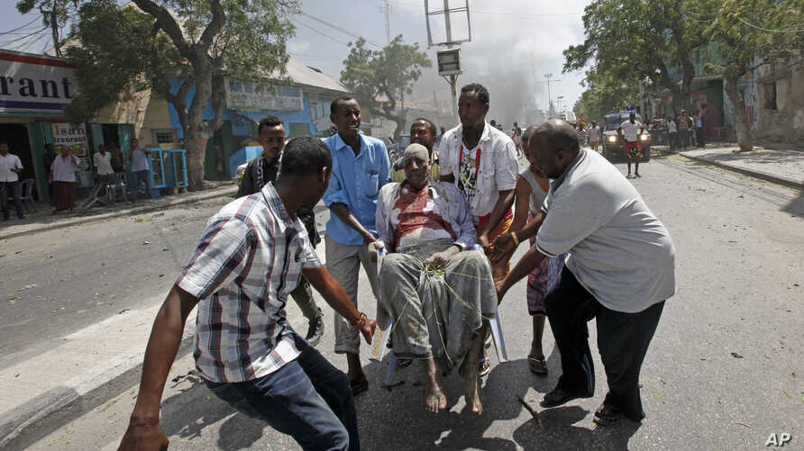 Rescuers carry away a man who was wounded in a car bomb attack in Mogadishu, Somalia, March 13, 2017.