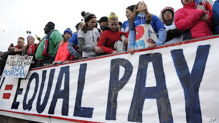 FILE - Fans stand behind a sign for equal pay for the women's soccer team during a match between the United States and Colombia, in East Hartford, Conn., April 6, 2016. The World Economic Forum's annual Global Gender Gap Report released, Oct. 25, 20