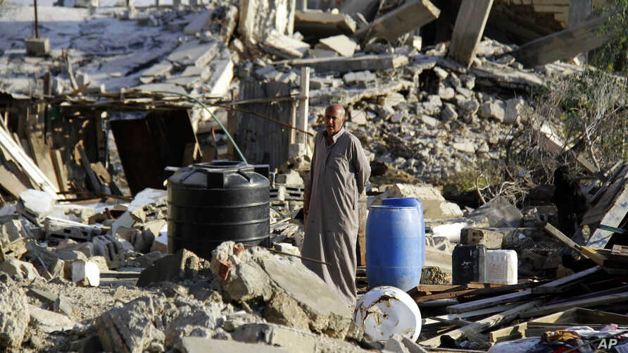 FILE - A man stands in the rubble off a home demolished by security forces on the on the Egyptian side of border town of Rafah, northeast of Cairo, Egypt, Nov. 6, 2014.