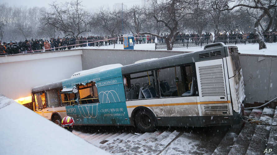 Pedestrians stand around the scene of a bus crash in Moscow, Russia, Dec. 25, 2017.