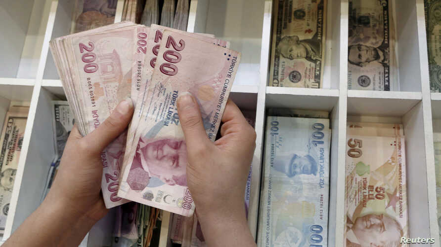 A money changer counts Turkish lira bills at an currency exchange office in central Istanbul, Turkey, Aug. 21, 2015. President Tayyip Erdogan's has asked Turks to convert their dollars and euros to lira.