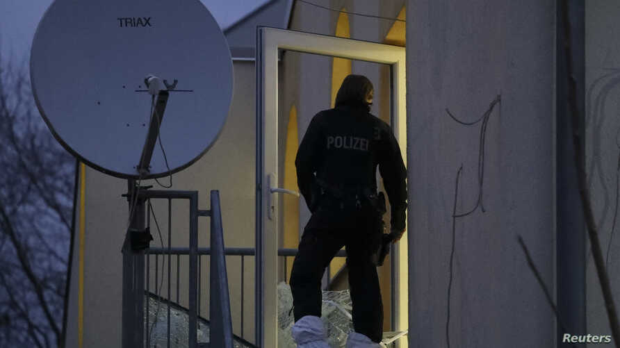 A German police officer stands in a smashed glass door of Frankfurt's Bilal mosque during early morning raids in the federal state of Hesse and its capital Frankfurt, Feb. 1, 2017.