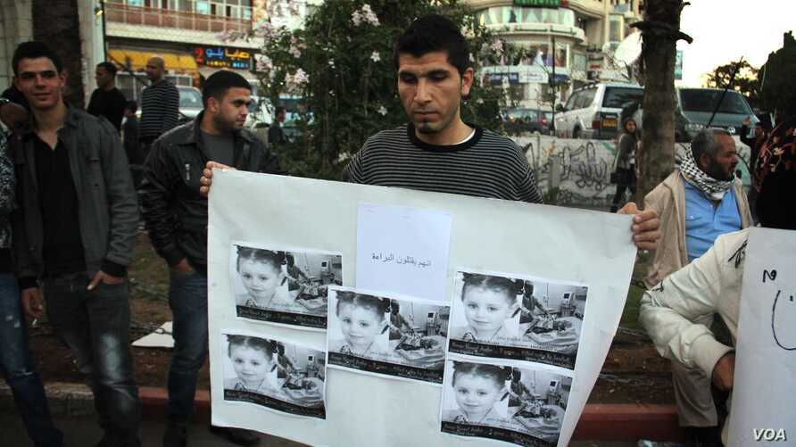 A protestor in Ramallah holds a picture of a young Gazan girl and says the violence must stop. He blames Israel but says his leadership must do more. (R.Collard/VOA)