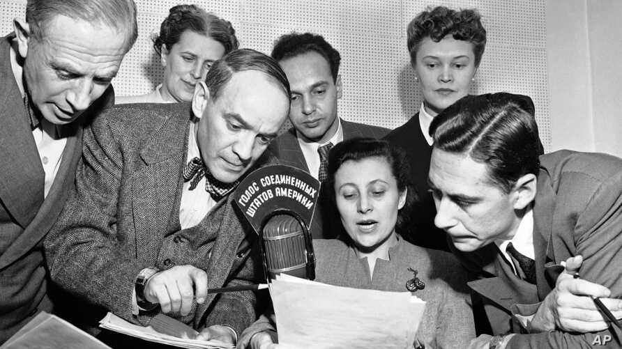 FILE - A group of State Department announcers huddle around the microphone after the initial shortwave broadcast in Russian to Russia from New York City, Feb. 17, 1947.