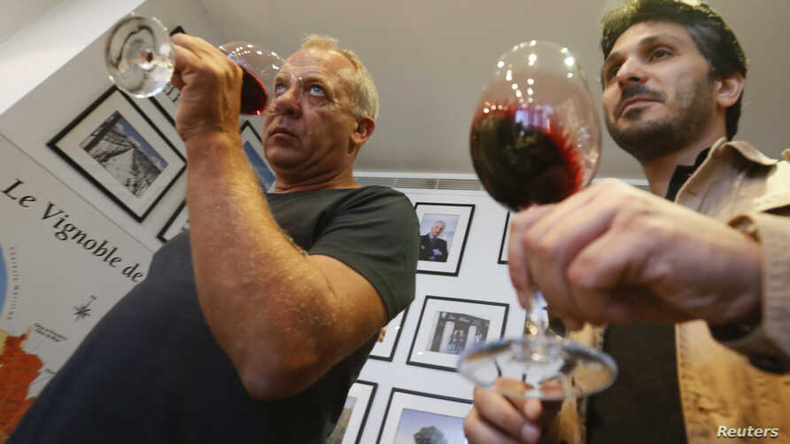 Sandro Saade (R), the owner of Domaine de Bargylus, and French winemaker and consultant Stephane Derenoncourt during a wine tasting session in Beirut, Sept. 3, 2014.