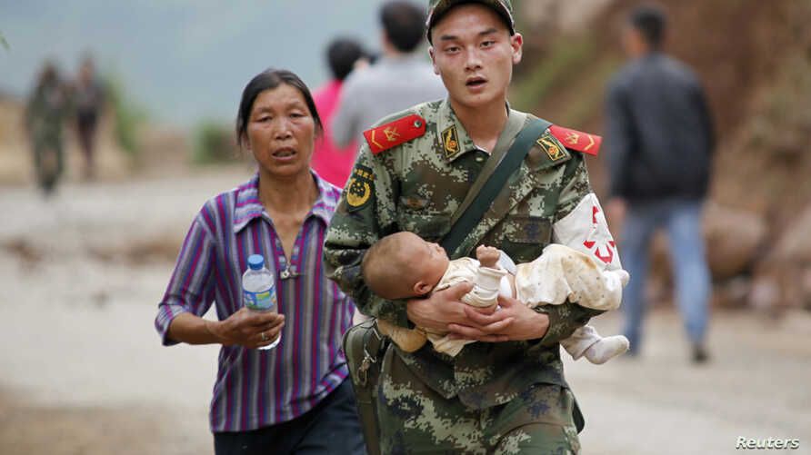A paramilitary policeman carries a baby in his arms after an earthquake hit Ludian county of Zhaotong, Yunnan province August 3, 2014.