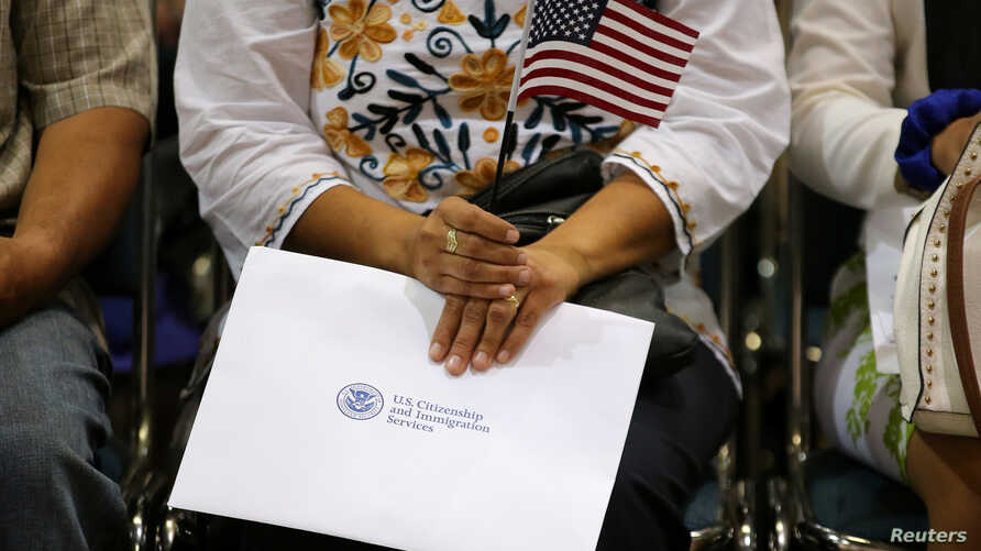 An attendee holds her new country's flag and her naturalization papers as she is sworn in during a U.S. citizenship ceremony in Los Angeles, U.S., July 18, 2017.