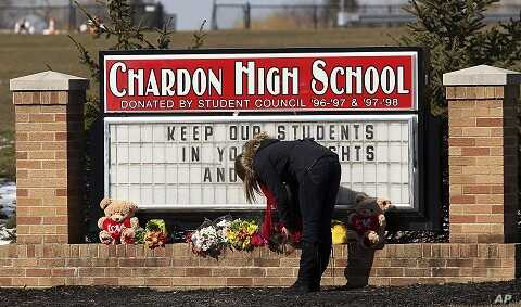 A female student places a bouquet of roses at the base of the Chardon High School sign in Chardon, Ohio February 28, 2012.