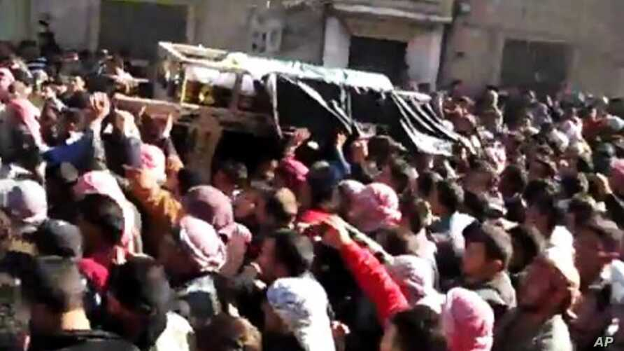 In this image from TV shown on the internet made available by the Sham News Network, protesters carry the body of Tamer Mutlaq in Homs, Syria, December 20, 2011.
