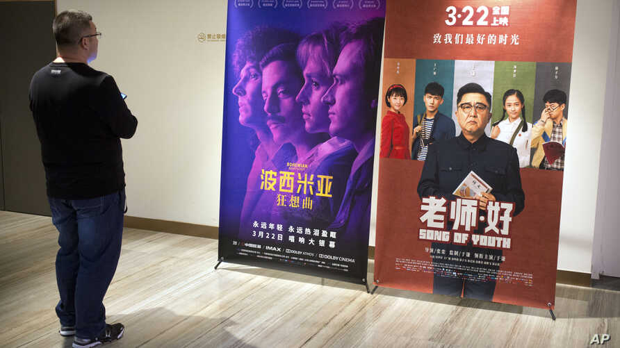 "A customer looks at a movie poster for the film ""Bohemian Rhapsody"" at a movie theater in Beijing, March 27, 2019."