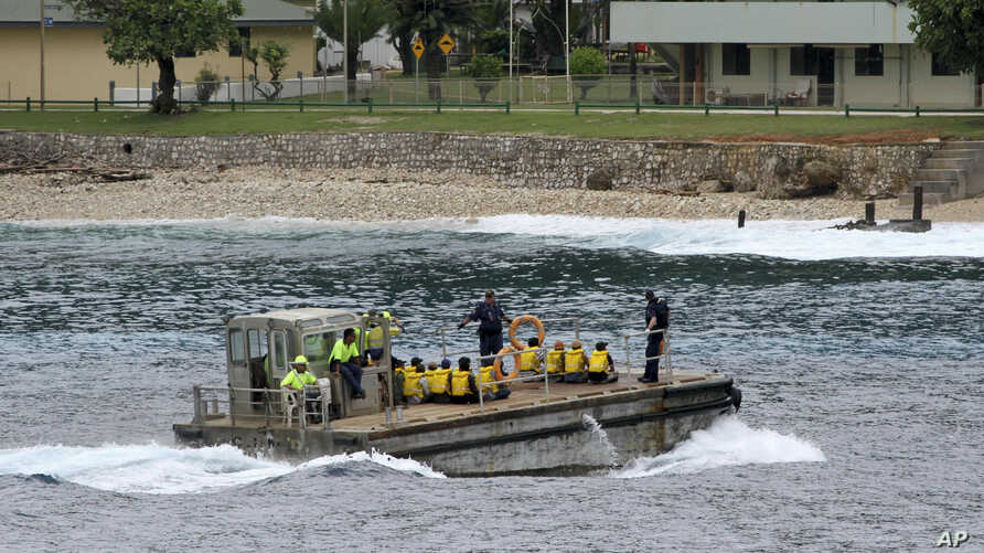 FILE - A group of Vietnamese asylum seekers are taken by barge to a jetty on Australia's Christmas Island, April 14, 2013.