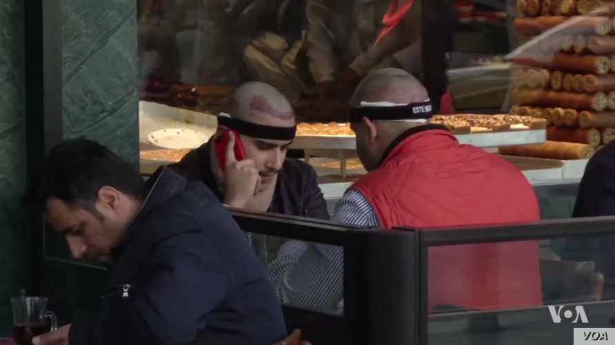 Men with bands around their heads from recent hair transplant surgery at a cafe in Istanbul's Taksim Square.