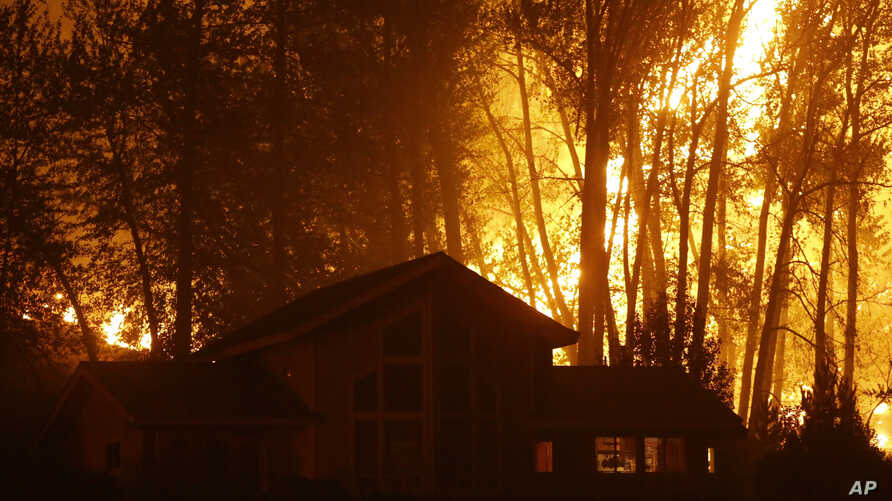 A wildfire burns behind a home on Twisp River Road, Aug. 20, 2015 in Twisp, Wash.