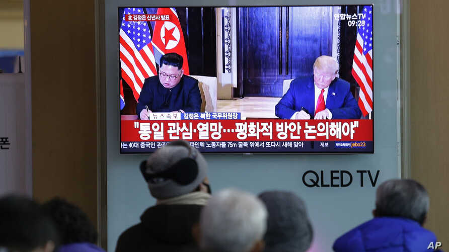 A TV shows a photo of U.S. President Donald Trump and North Korean leader Kim Jong Un, left, while people listen to Kim's New Year's speech, at Seoul Railway Station in Seoul, South Korea, Jan. 1, 2019.