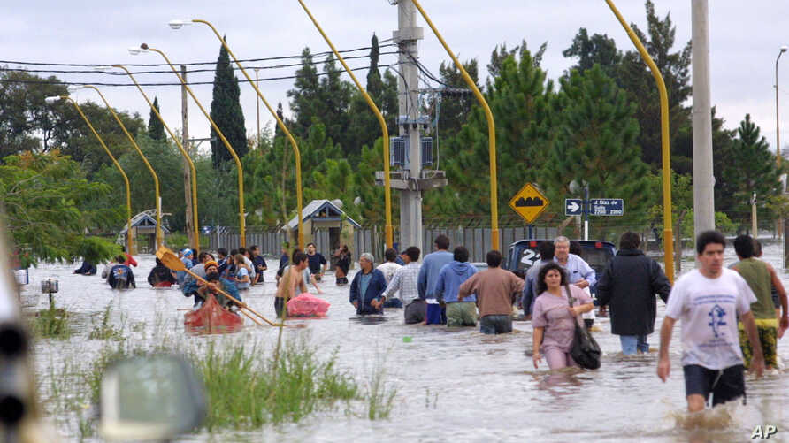 FILE - People walk in the water as they leave the flooded area of Santa Fe, some 390 kilometers, (250 miles) northwest of Buenos Aires, Argentina, April 30, 2003.