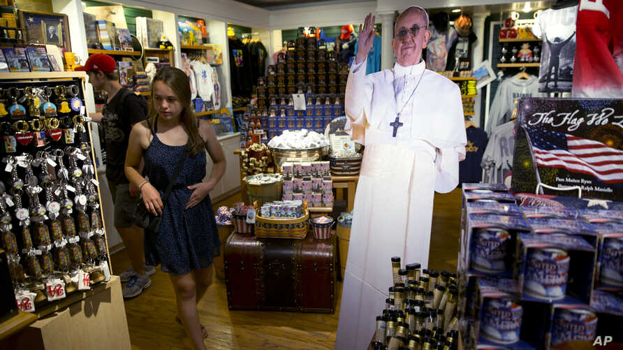A tourist passes cutout of Pope Francis at Making History, a Philadelphia themed gift shop Philadelphia, Aug. 10, 2015. The cutouts have been popping up in areas around the region more than a month ahead of the pope's scheduled visit.