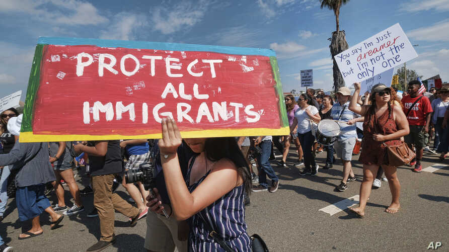 FILE - Supporters of the Deferred Action for Childhood Arrivals, or DACA chant slogans and carry signs while joining a Labor Day rally in downtown Los Angeles.