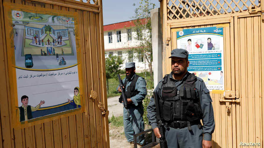 Afghan policemen stand guard at a gate of a voter registration center for the upcoming parliamentary and district council elections in Kabul, Afghanistan, April 23, 2018.