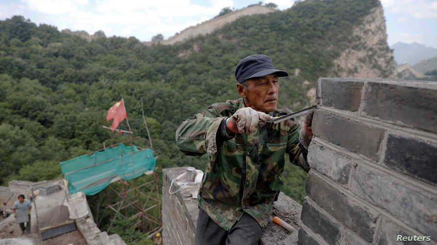 People work on the reconstruction of the Jiankou section of the Great Wall, located in Huairou District, north of Beijing, China, June 7, 2017.