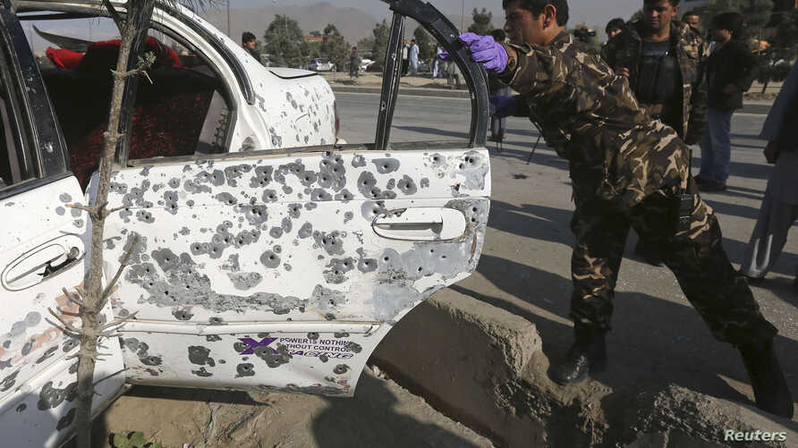 A member of Afghan security force investigates a vehicle damaged by a remote-controlled bomb, at the site of an incident in Kabul, Oct. 14, 2014.