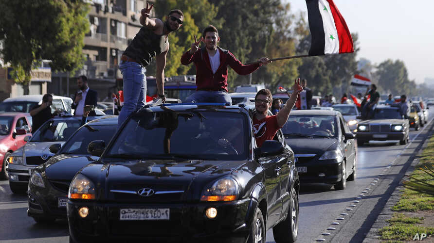Syrian government supporters wave national flags and chant slogans against U.S. President Trump during demonstrations following a wave of U.S., British and French military strikes to punish President Bashar Assad for suspected chemical attack against