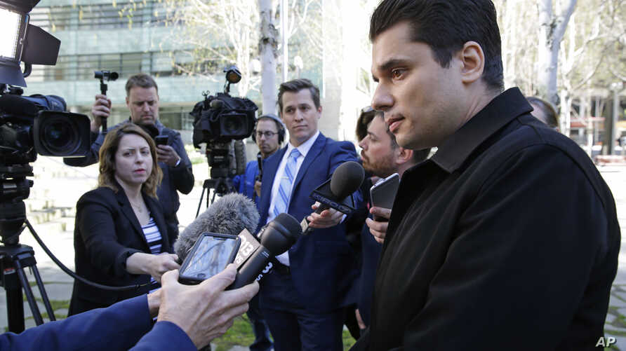 Igor Litvak (right) the attorney for Russian hacker Roman Seleznev, talks to reporters, April 21, 2017, in Seattle, following the federal court sentencing of Seleznev to 27 years in prison after he was convicted of hacking into U.S. businesses to ste