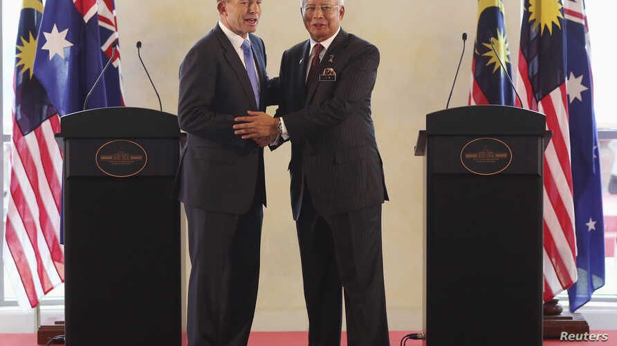 Australian Prime Minister Tony Abbott (L) and his Malaysian counterpart Najib Razak shake hands at a joint news conference in Putrajaya, Sept. 6, 2014.
