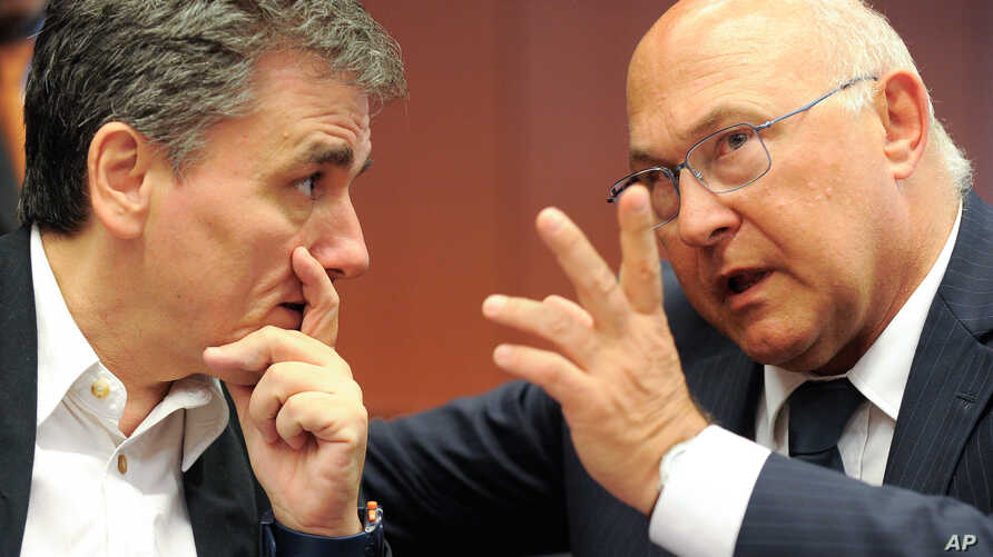 French Finance Minister Michel Sapin talk to Greek Finance Minister Euclid Tsakalotos, left, during a meeting of eurozone finance ministers at the EU Council building in Brussels, Aug. 14, 2015.