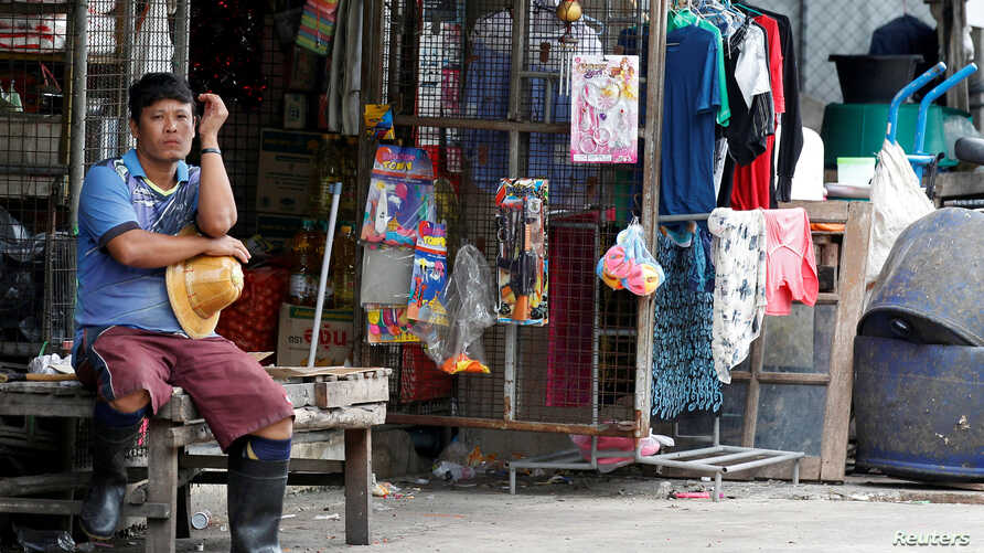 FILE - A Myanmar migrant worker rest outside his house near a wholesale market for shrim and other seafood in Mahachai, in Samut Sakhon province, Thailand, July 4, 2017.