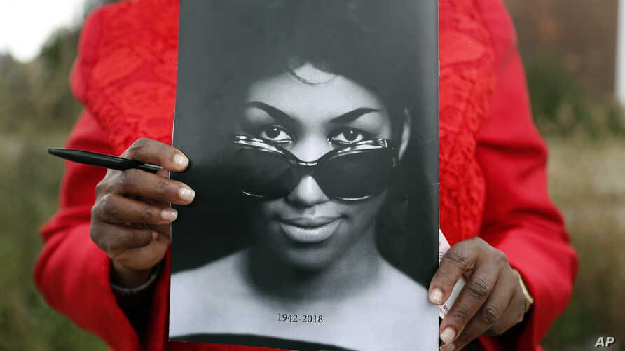 Sharon Napoleon holds a program as she stands outside a viewing for legendary singer Aretha Franklin at New Bethel Baptist Church, Aug. 30, 2018, in Detroit. Franklin died Aug. 16, 2018, of pancreatic cancer at age 76.