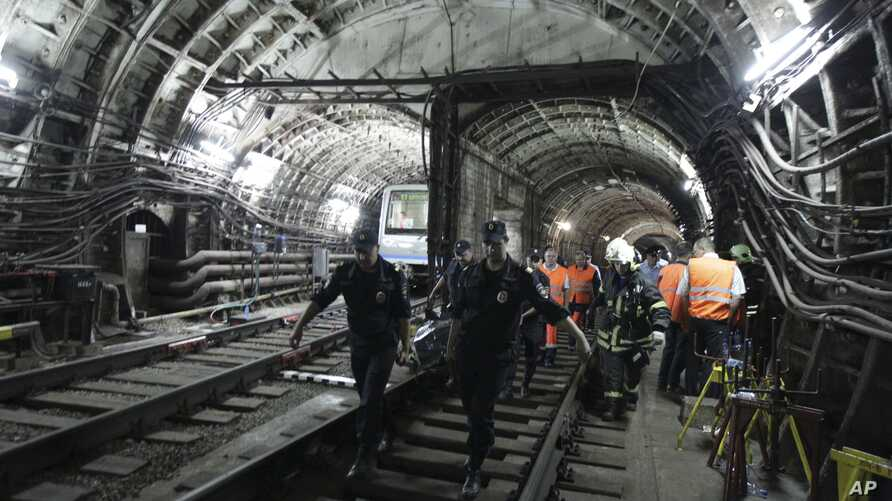 In this photo taken on July 15, 2014 rescuers carry a stretcher with a victim from a tunnel after a train derailed between two subway stations in Moscow, Russia.