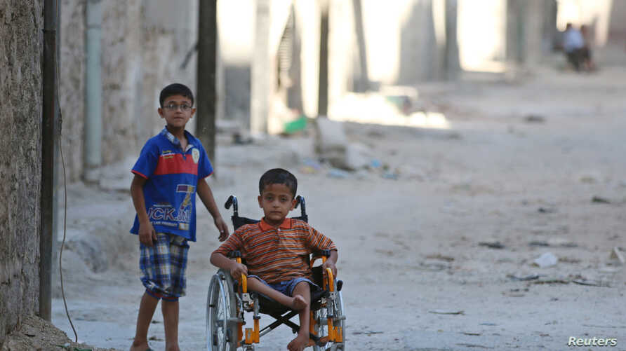 Boys, one of them in a wheelchair, venture down a street in the al-Sheikh Said neighborhood of Aleppo, Syria, Sept. 1, 2016.
