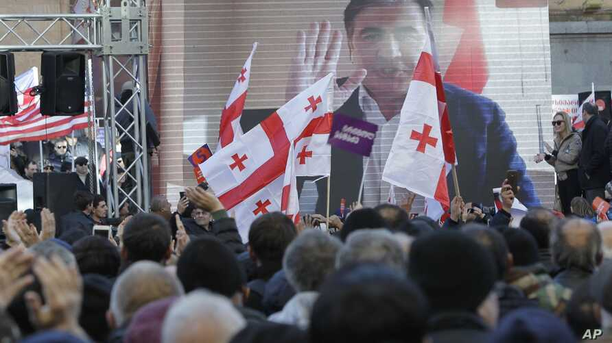 Supporters of opposition candidate Grigol Vashadze watch a live with former Georgian President Mikheil Saakashvili on a big screen during a rally in Tbilisi, Georgia, Dec. 2, 2018.