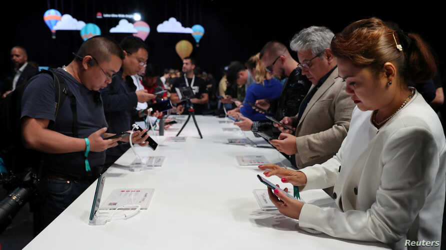 FILE - People look at display models of the Huawei Mate20 smartphone series at a launch event in London, Britain, Oct. 16, 2018.