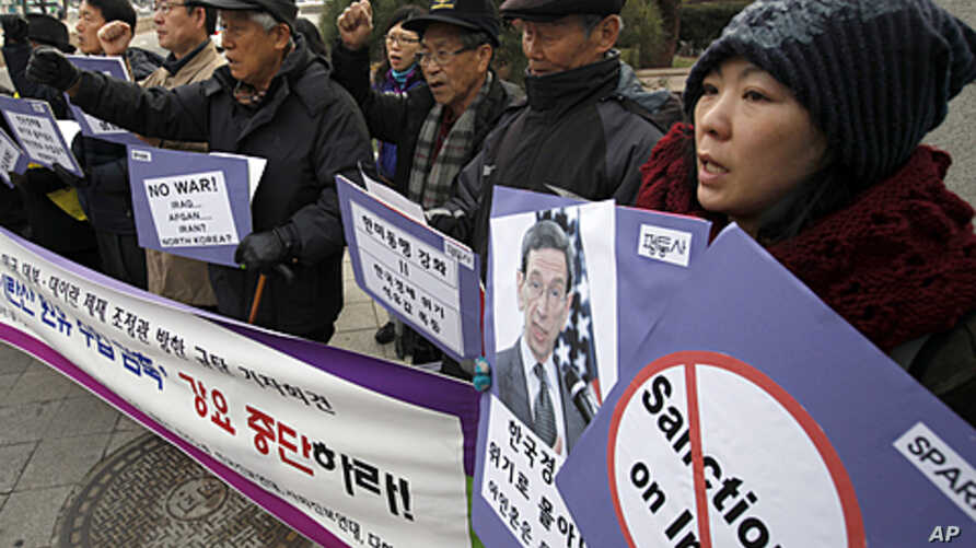 Activists chant slogans during a news conference denouncing U.S. sanctions on Iran in front of the foreign ministry, where the U.S. State Department's special adviser for nonproliferation and arms control, Robert Einhorn is to meet South Korean Deput