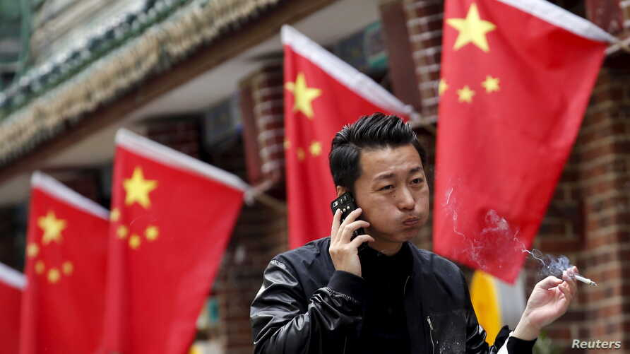 FILE: A smoker puffs while passing a restaurant in Beijing, May 11, 2015. The country enforced vast new rules on tobacco advertising Sept. 1.
