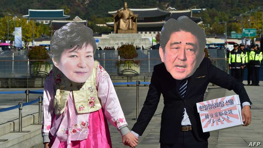 Protesters wearing masks depicting South Korean President Park Geun-Hye (L) and Japanese Prime Minister Shinzo Abe (R) hold hands during an anti-Japanese rally in Seoul, Oct. 30, 2015.