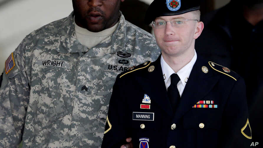 Army Pfc. Bradley Manning, right, is escorted out of a courthouse in Fort Meade, Maryland, June 25, 2012.