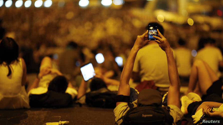A protester takes pictures of fellow demonstrators as they block the main street to Hong Kong's financial Central district, September 29, 2014.