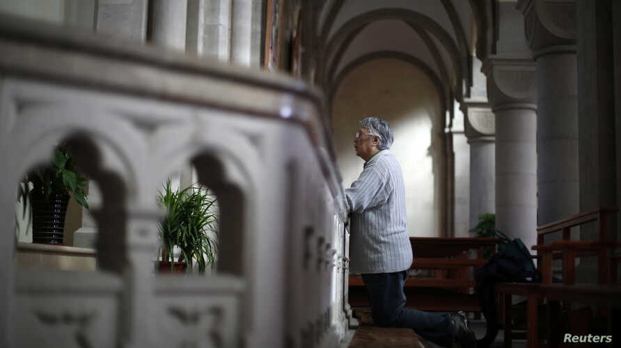 A woman prays at Sheshan Cathedral in the outskirts of Shanghai October 28, 2013. Picture taken on October 28, 2013