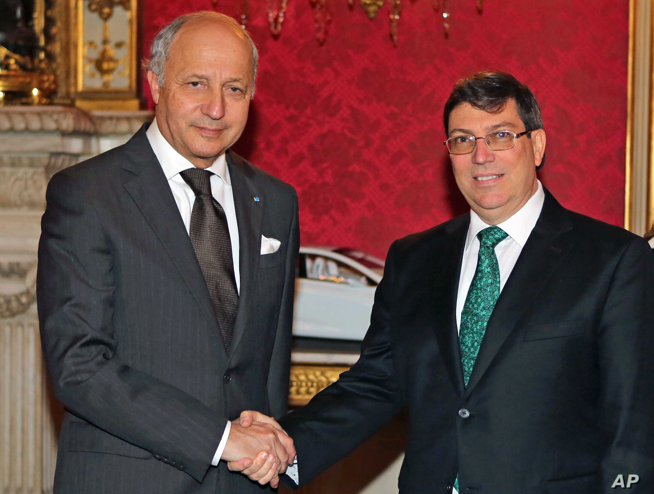 French Foreign Minister Laurent Fabius (l) greets his Cuban counterpart Rodriguez Parilla, prior to their meeting at the foreign ministry in Paris, March 14, 2014.