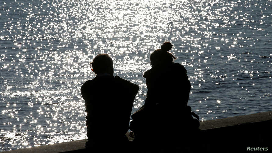 A couple is silhouetted at the harbor of Livorno, central Italy, Feb. 14, 2017.