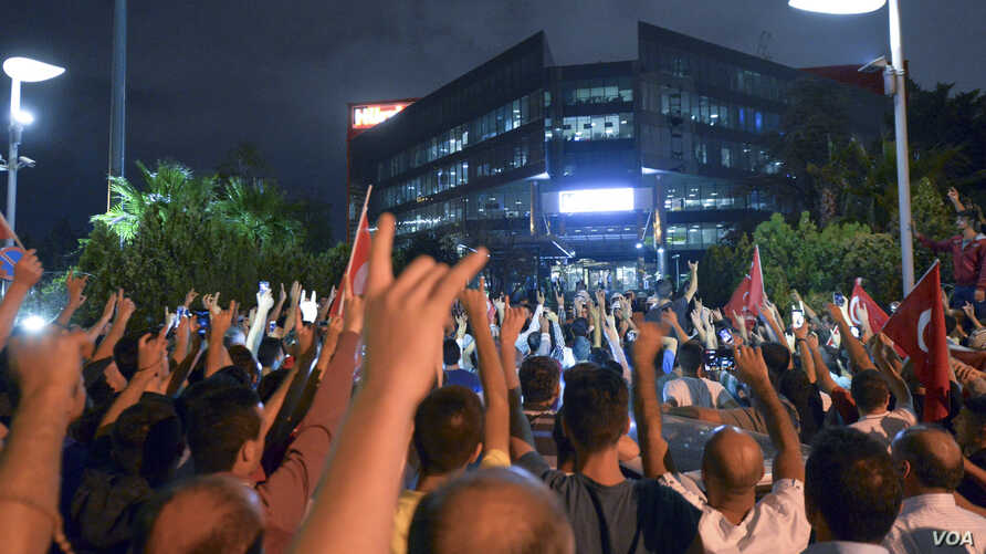 A group of people stage a protest outside the Hurriyet newspaper in Istanbul, Turkey, late Tuesday, Sept. 8, 2015.