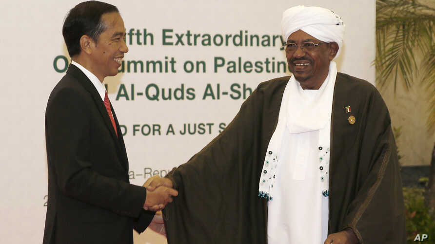 """Indonesian President Joko """"Jokowi"""" Widodo, left, greets his Sudanese counterpart Omar al-Bashir upon his arrival for the extraordinary Organization of Islamic Cooperation (OIC) summit on Palestinian issues in Jakarta, Indonesia, Monday, March 7, 2016"""